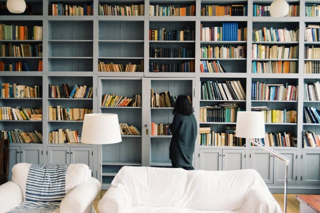 Room full of books on a shelf with a white couch and a woman looking for a book