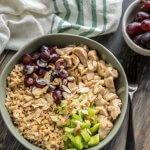 A bowl of chicken salad and brown rice with grapes and celery