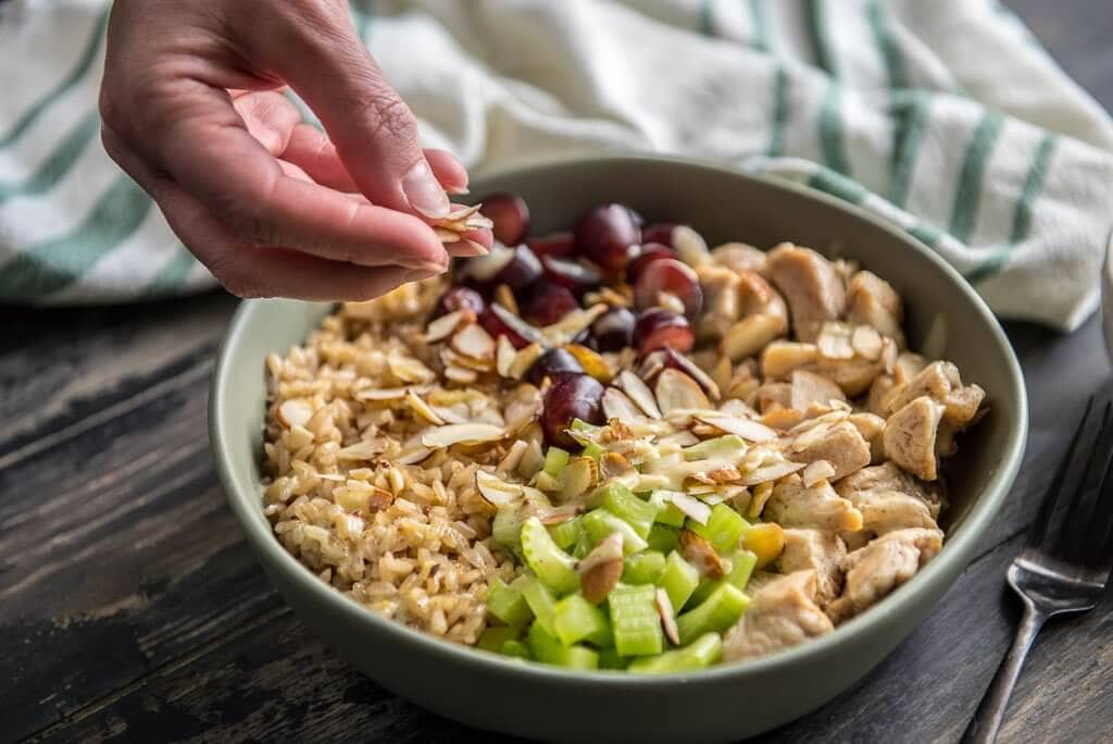 Bowl of healthy chicken salad brown rice bowl with grapes and celery and a woman placing almonds on top of the bowl.