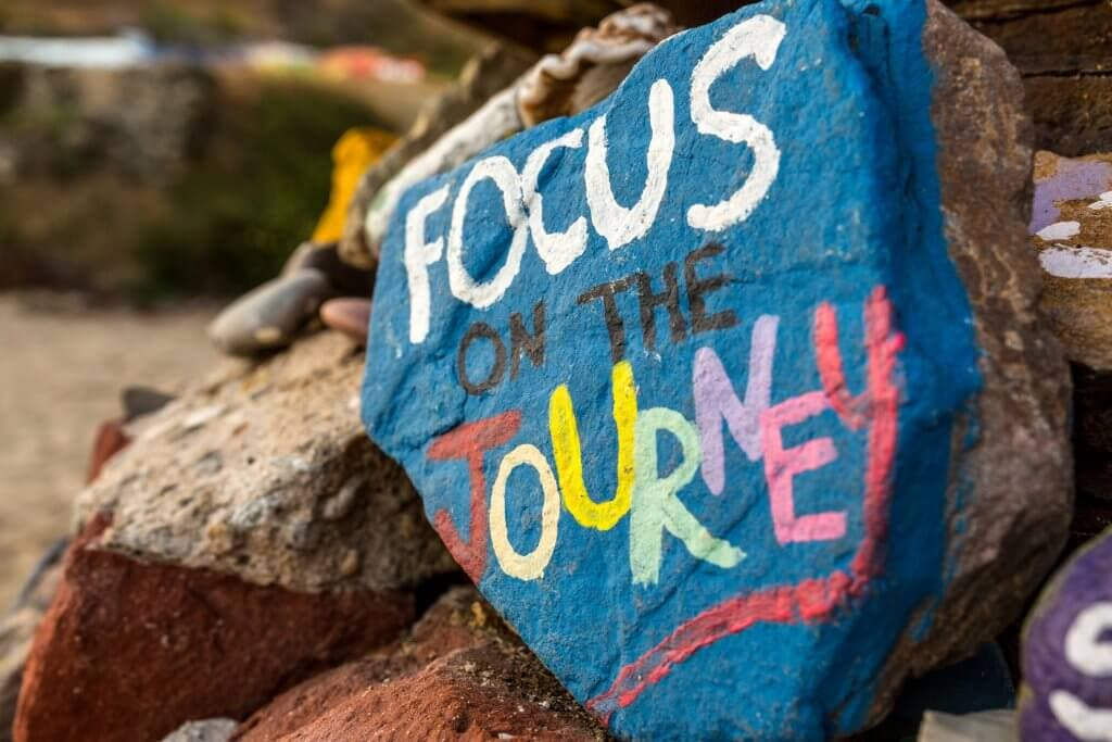 Focus on the journey written on a blue rock