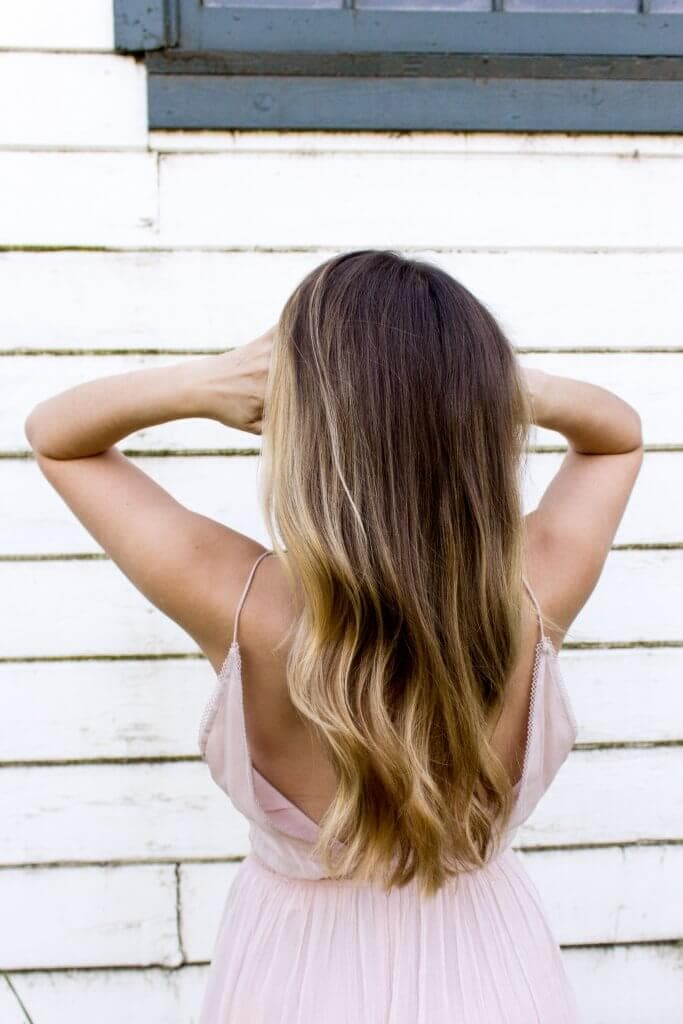 A lady with her back turned and her hands in her hair