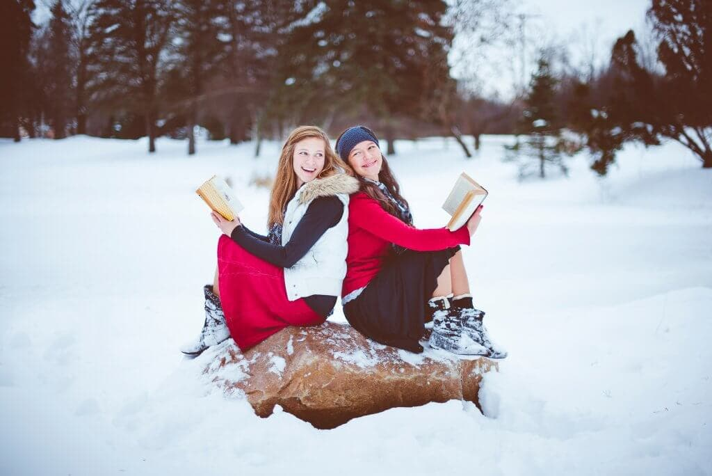 Two girls reading books in the snow and laughing