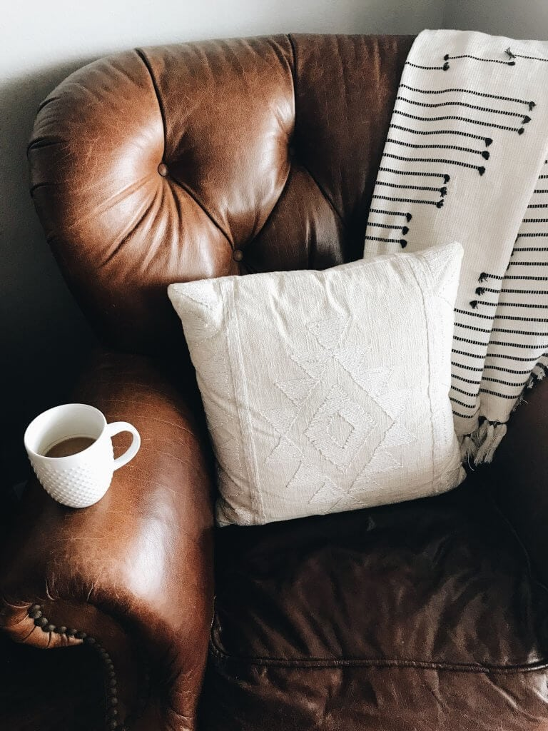 Brown chair with blankets and a pillow and coffee cup.