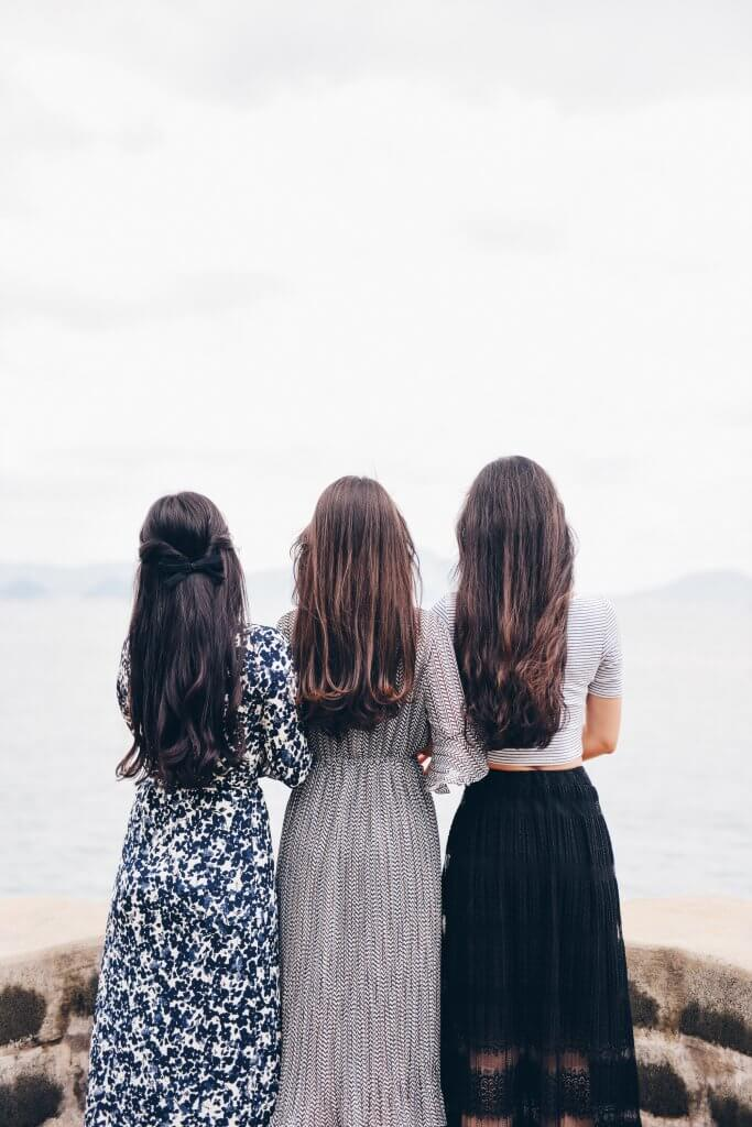 3 brunette girls with long hair overlooking an ocean wearing dresses