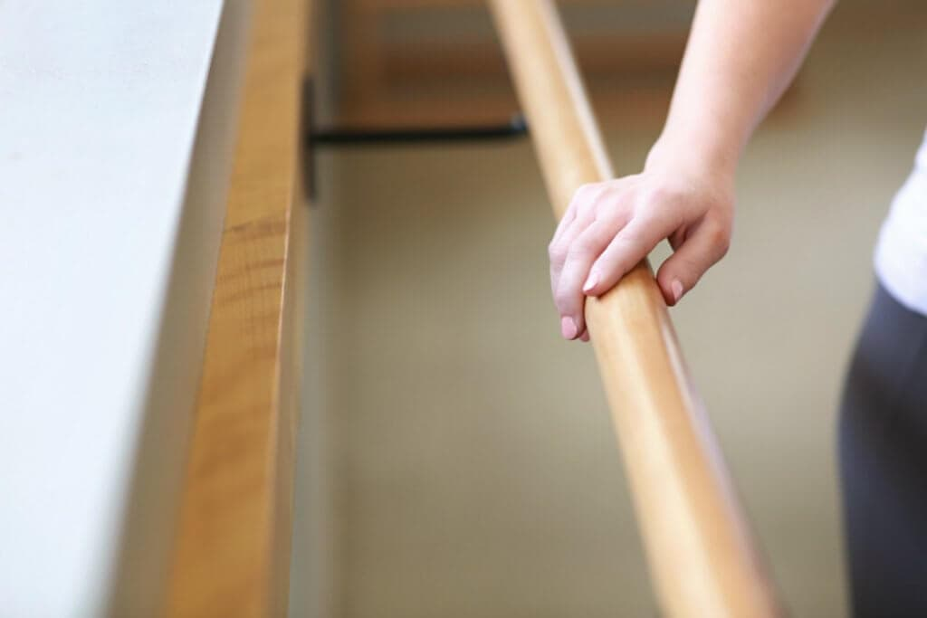 Womans hand on a barre during her workout routine