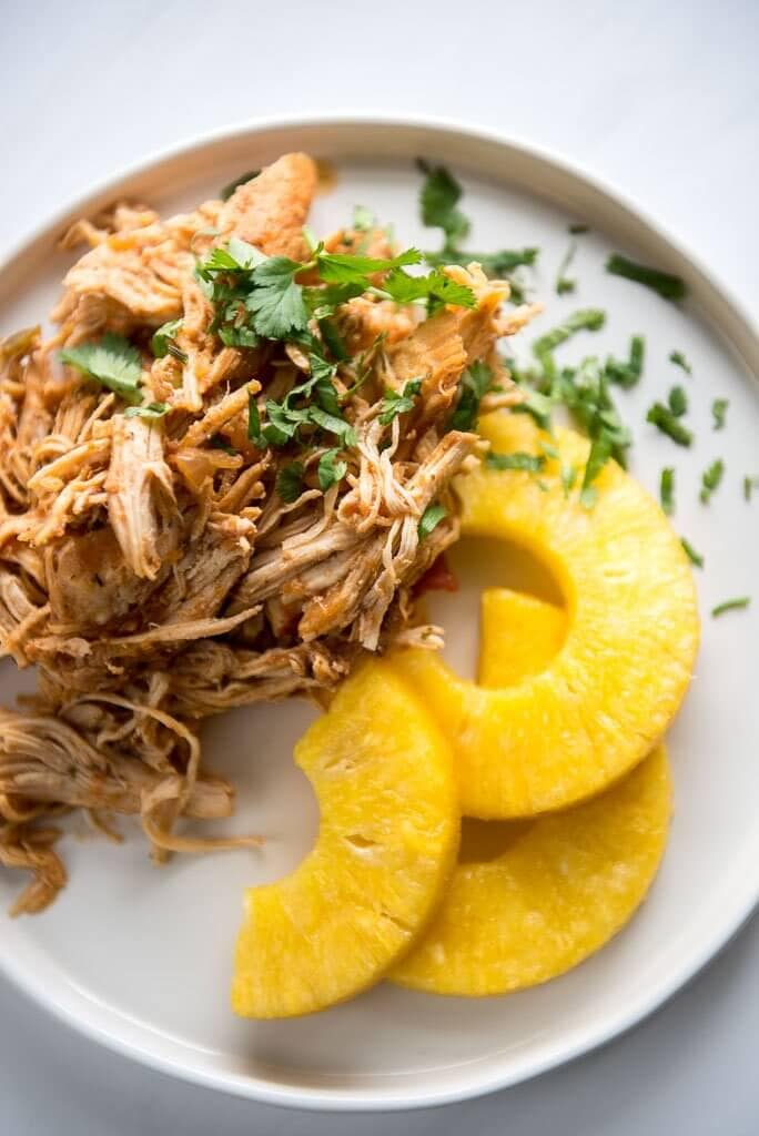Slow Cooker Salsa Chicken on a white plate with slices of pineapple and garnished with cilantro