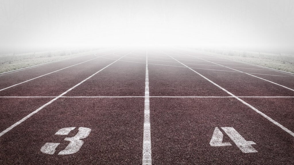 Starting line on a track with the 3rd and 4th lanes and a foggy day.