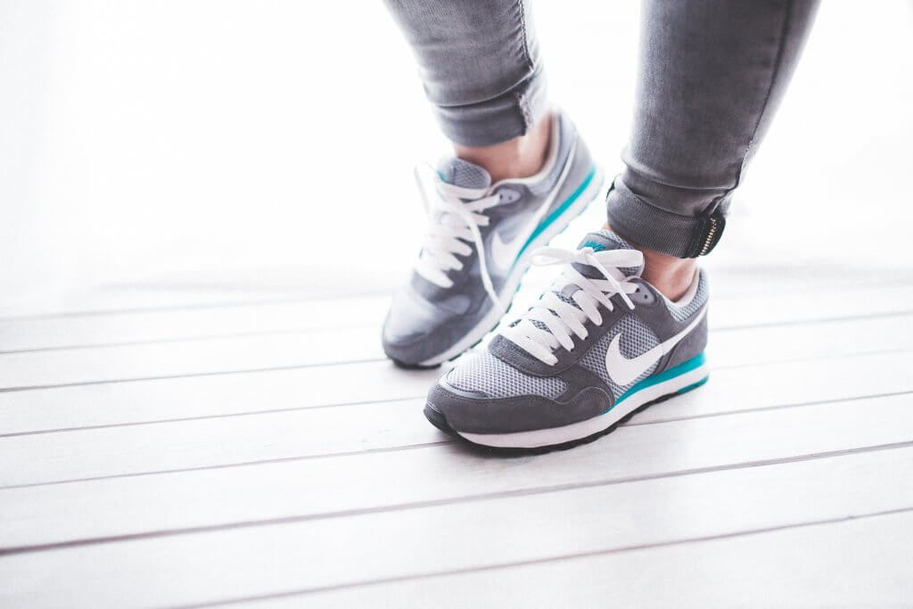 A woman in shoes on a white floor before starting her workout routine