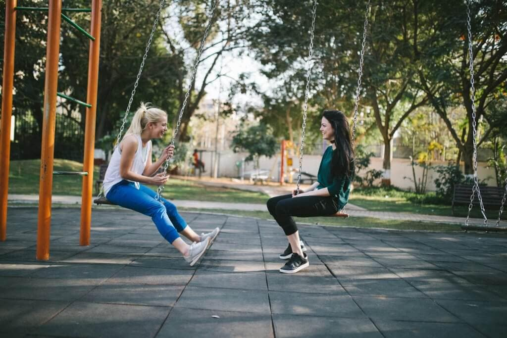 Two girls on swings talking and laughing
