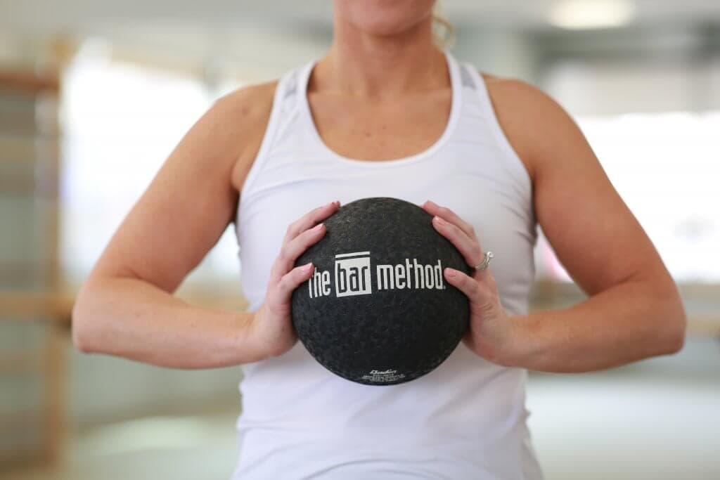 A woman in a white tank holding a Bar Method ball.