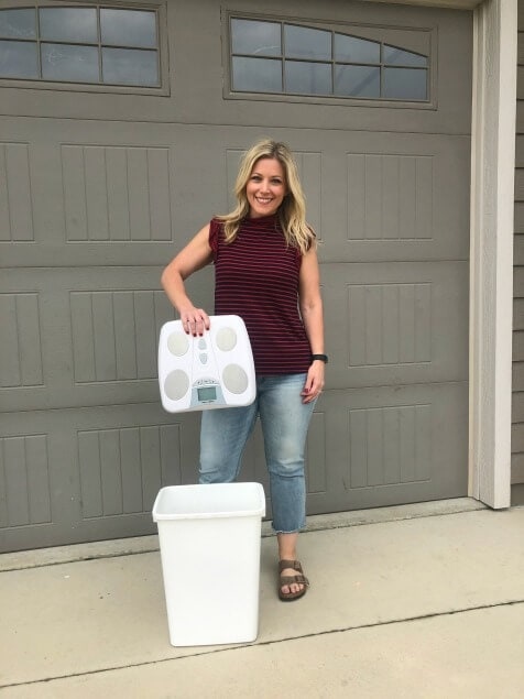 A woman holding a scale over a trash can