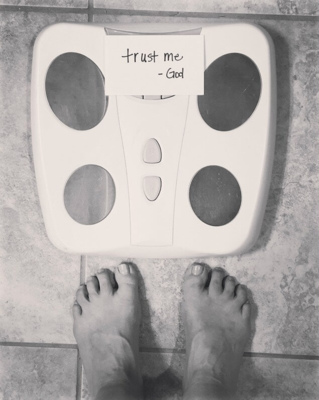black and white photo of a scale with trust me god written over the number
