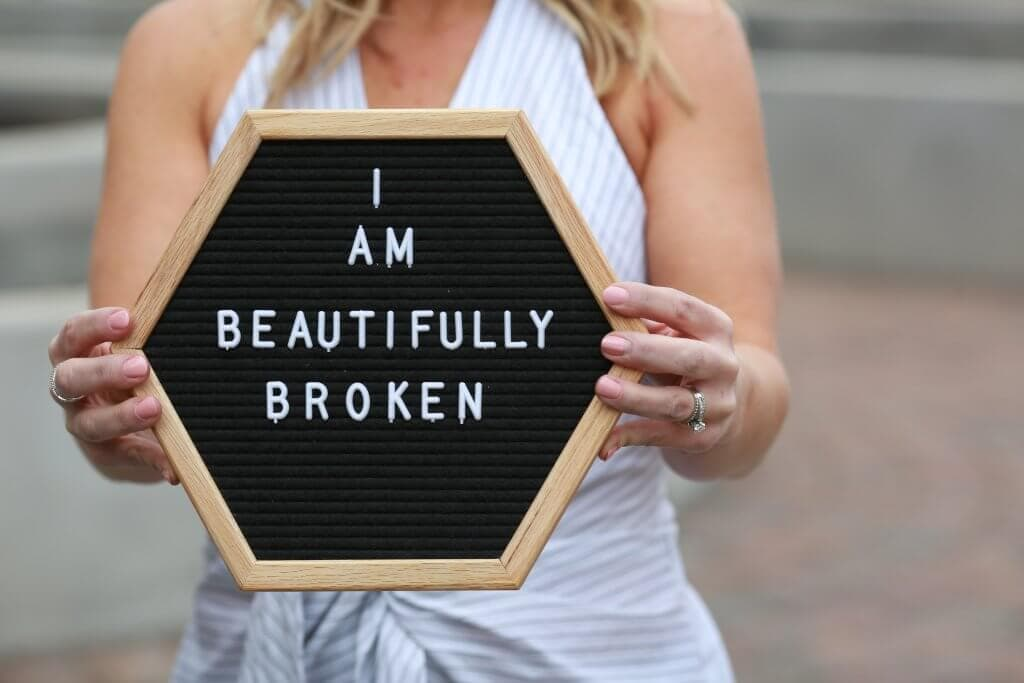 A woman holding a sign that says I am Beautifully Broken