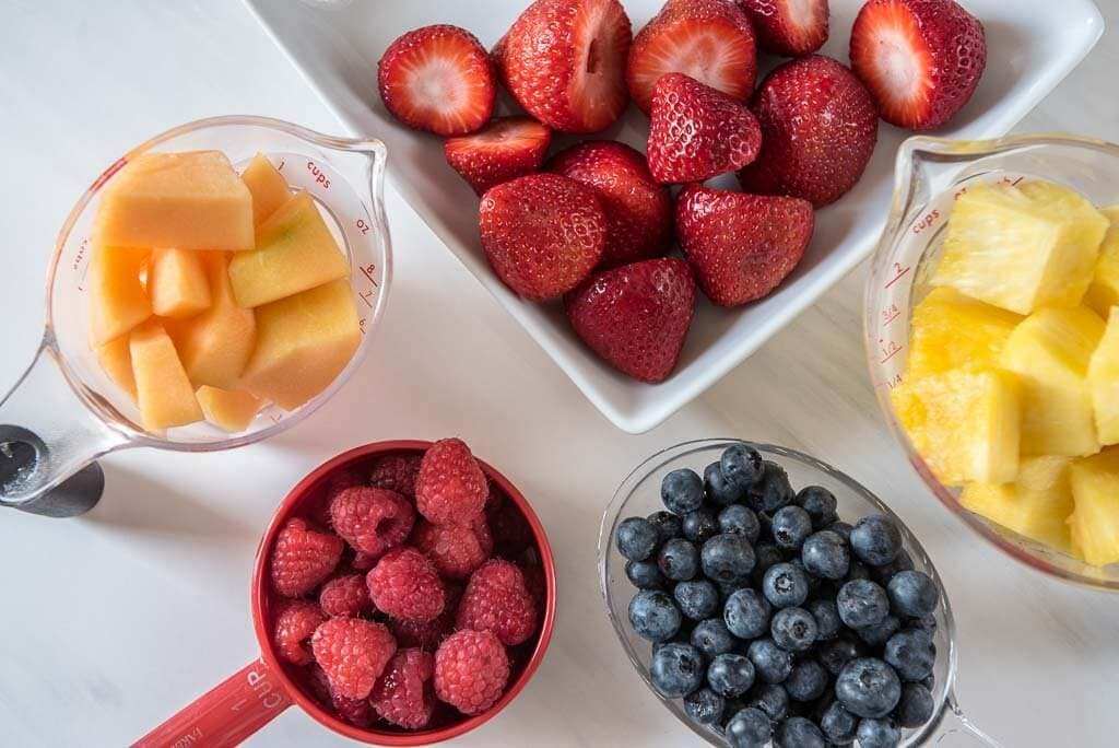 Dishes filled with Cantaloupe, strawberries, raspberries, blueberries, pineapple