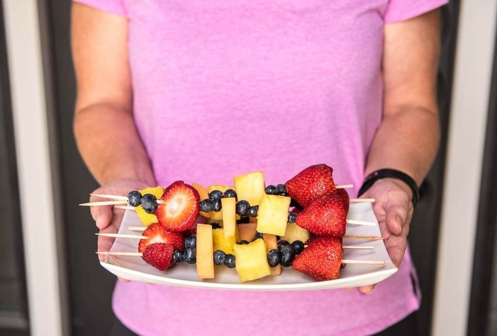 A woman holding a plate of fruit kabobs