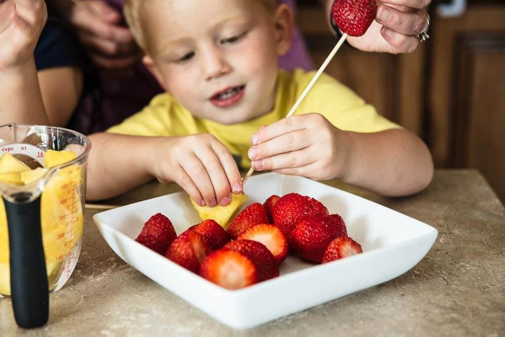 Young boy in a yellow shirt making a fruit kabob with a strawberry