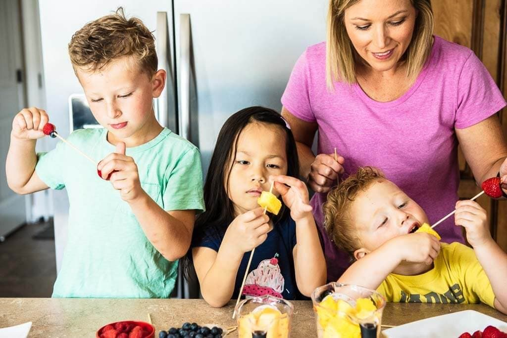 Adult and three children making fruit kabobs