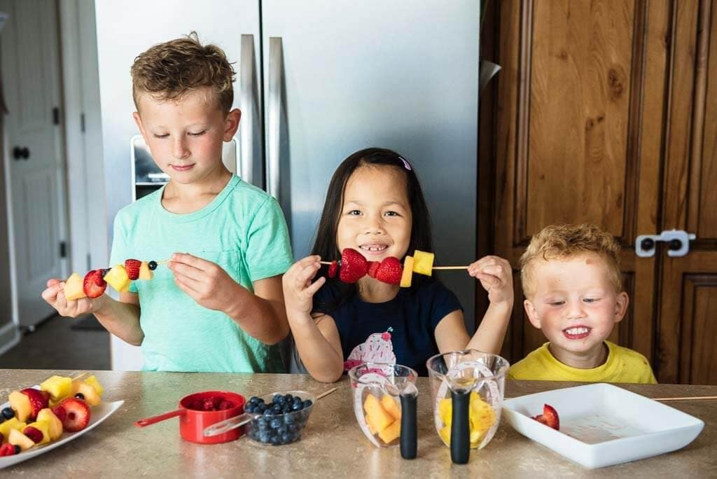 Two boys and a girl making fruit skewers
