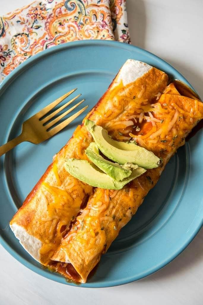 Serving of two pulled pork enchiladas on a blue plate with a napkin and a gold fork garnished with avocados