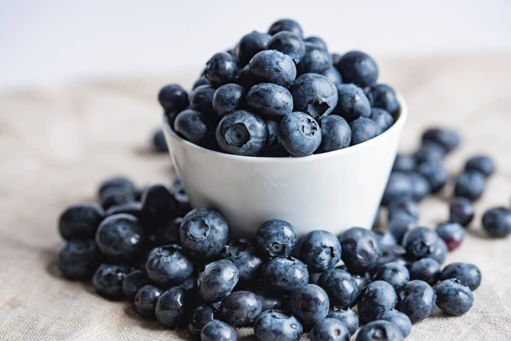 Blueberries in a white bowl with blueberries on the table