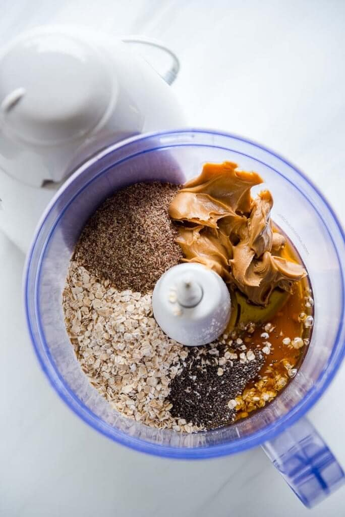 Overhead view of a food processor with oats, flax, chia, honey and pb