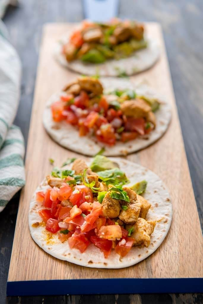 Photo of 3 cajun chicken street tacos on a wooden platter. The first taco is in focus and the other two are out of focus.