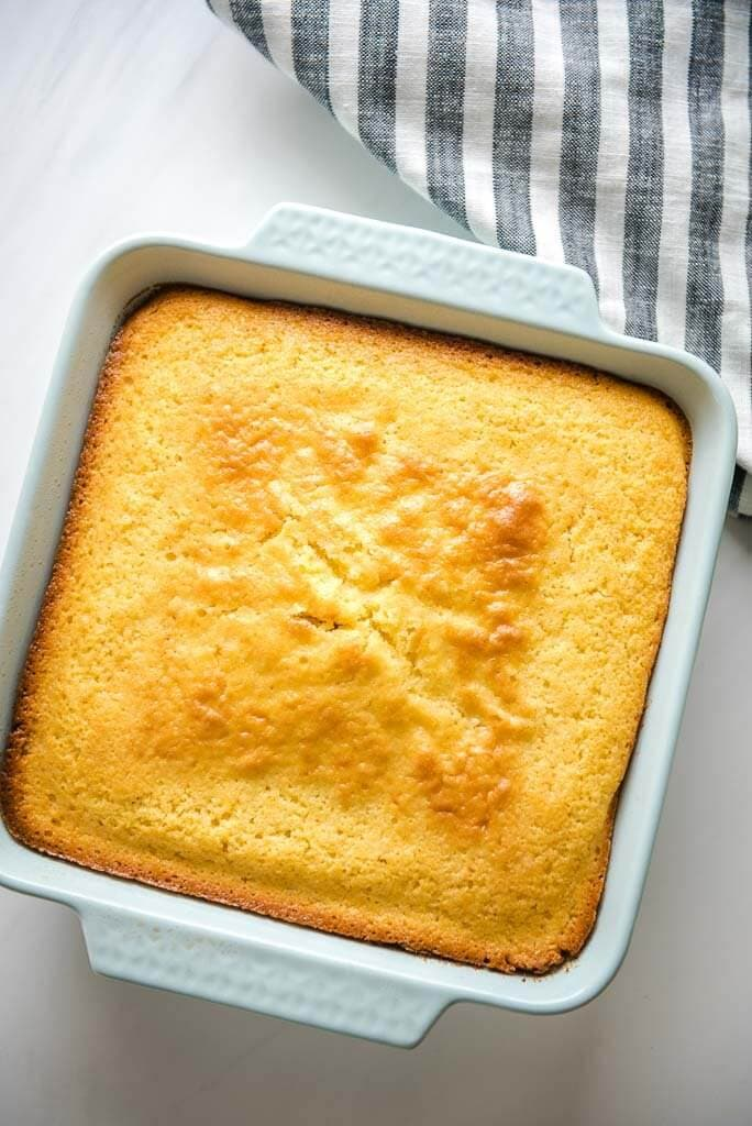 A pan of cornbread with a grey and white linen