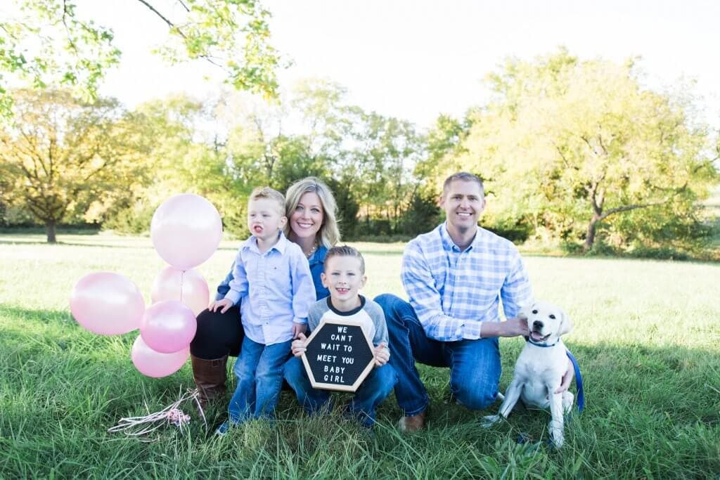 A family of four and their labrador announcing they are having a girl.