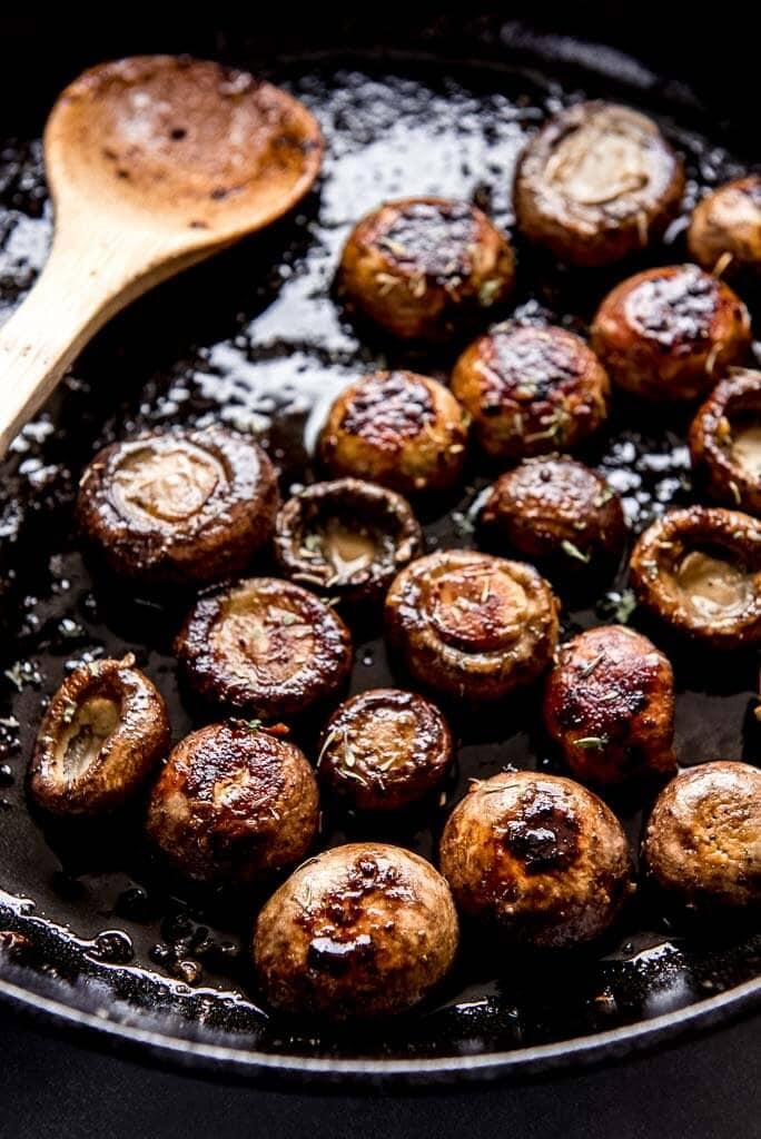 Sautéed mushrooms with a wooden spoon