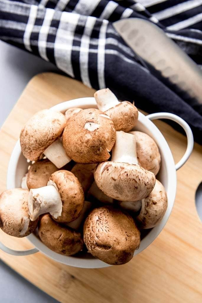 Washed Mushrooms in a strainer on a cutting board wth a knife and napkin