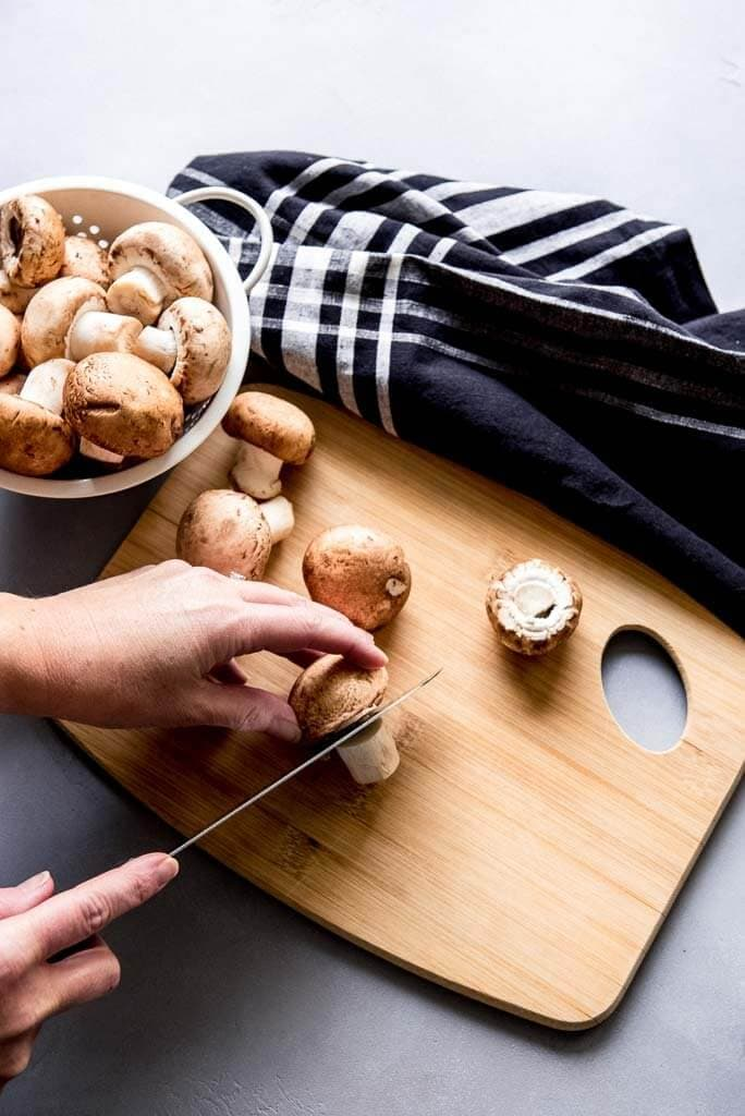 Woman cutting stems off mushrooms on a wooden cutting board with a napkin