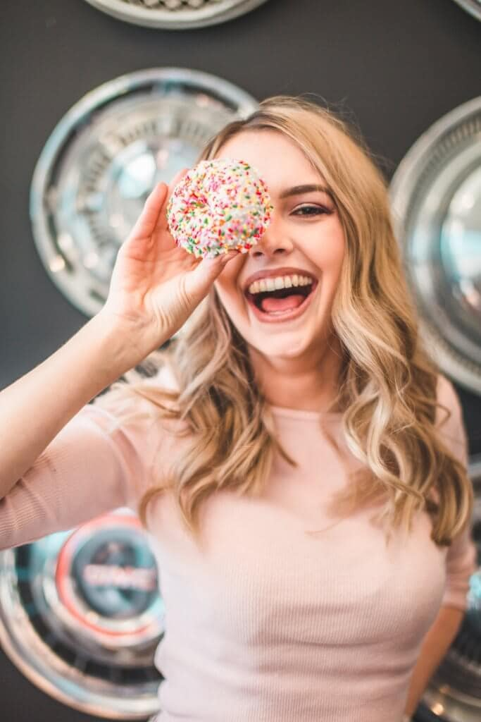 A woman with blonde hair and a pink top holding a donut in front of her face and smiling.