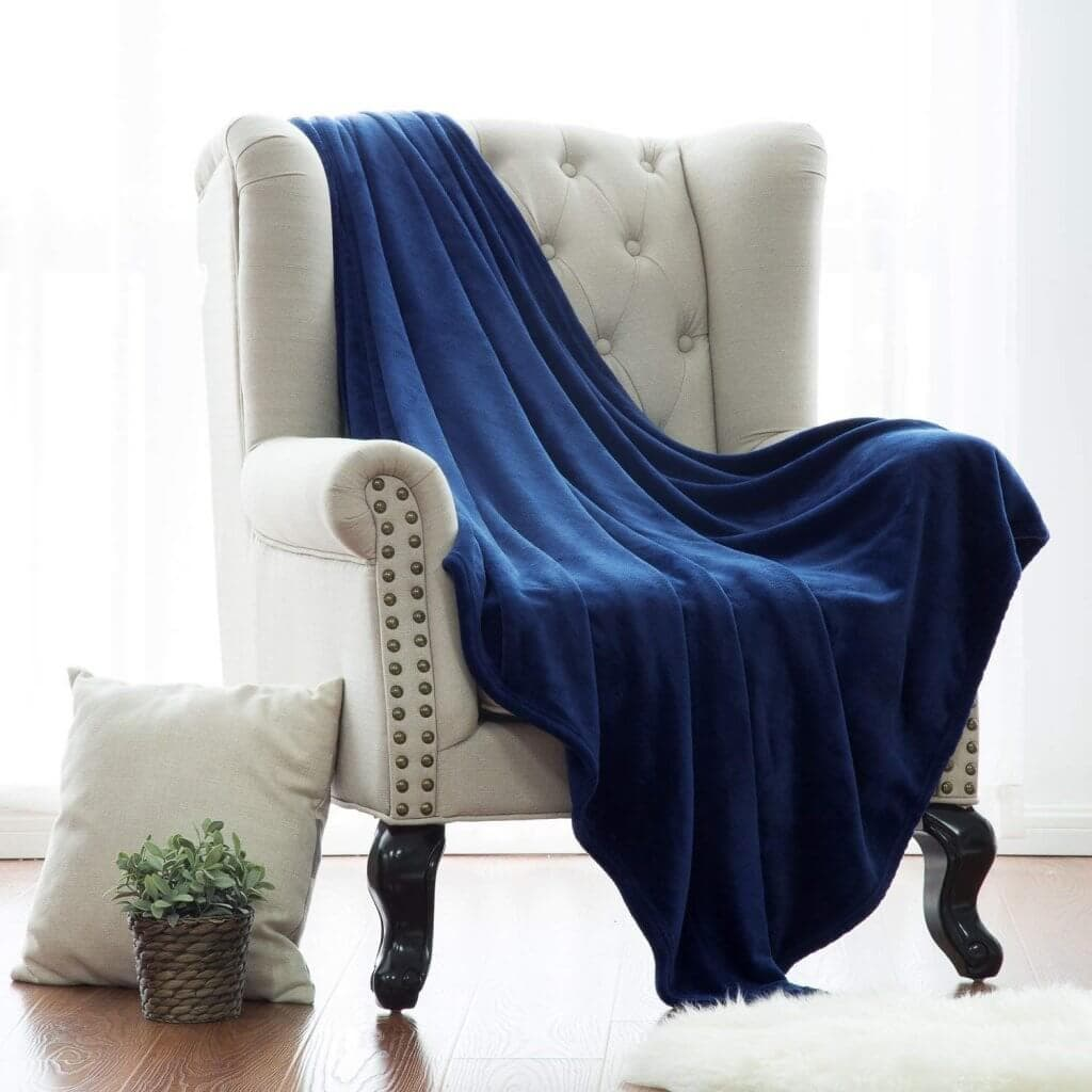 A white chair with a pillow and plant on the floor and a blue blanket draped over the chair
