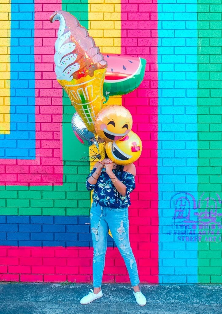 A bright colored wall with a woman holding balloons in front of her face. Smiley face, ice cream and watermelon balloons.