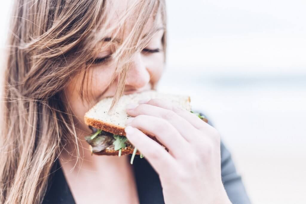 A brunette eating a sandwich