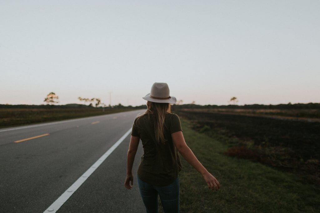 A woman walking on a road with her back turned and a hat on