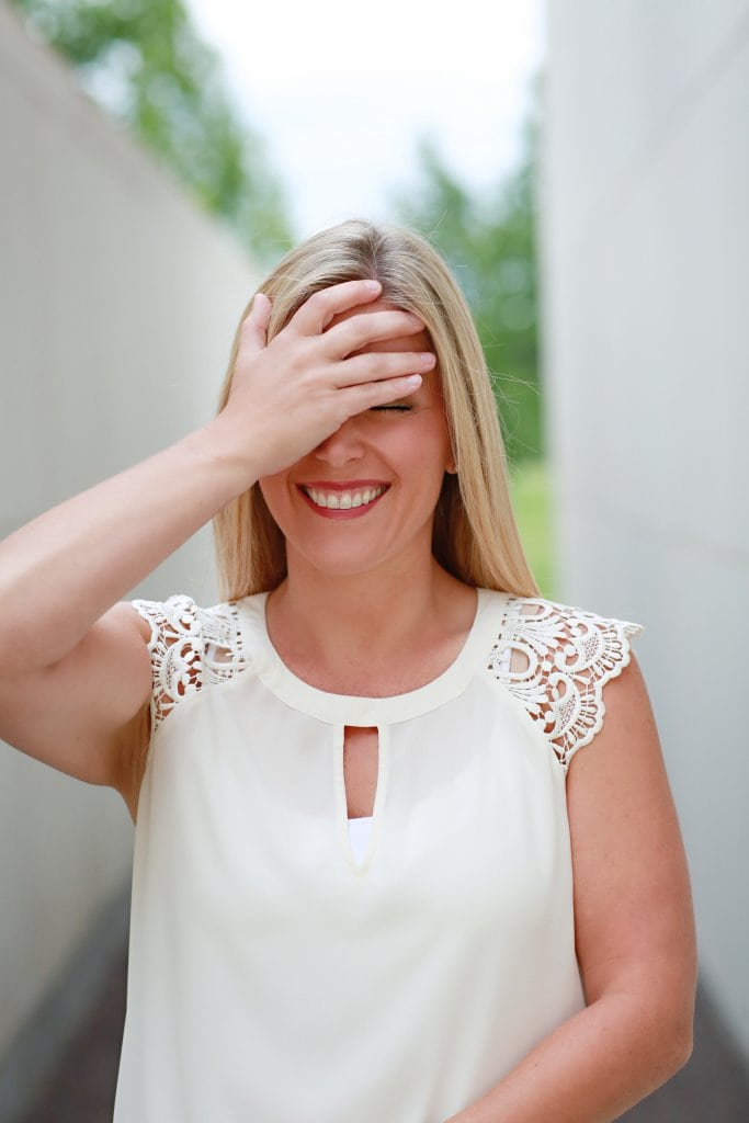 A girl holding her face and laughing