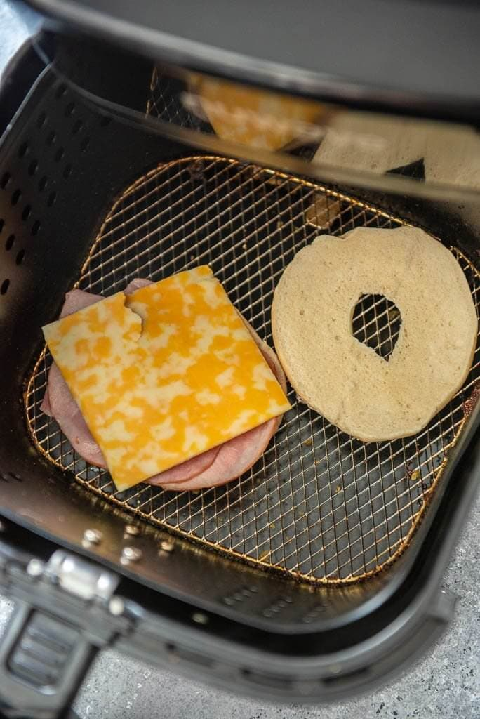 Air fryer basket with a bagel in it with ham and cheese on one side of the sliced bagel