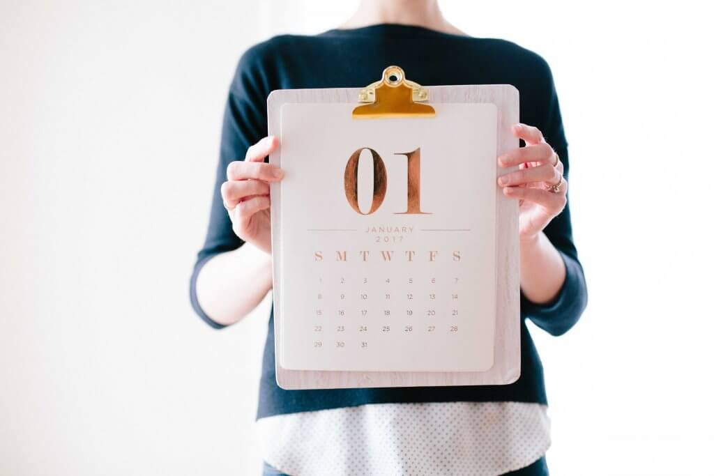 A woman holding a calendar with January 1st on it