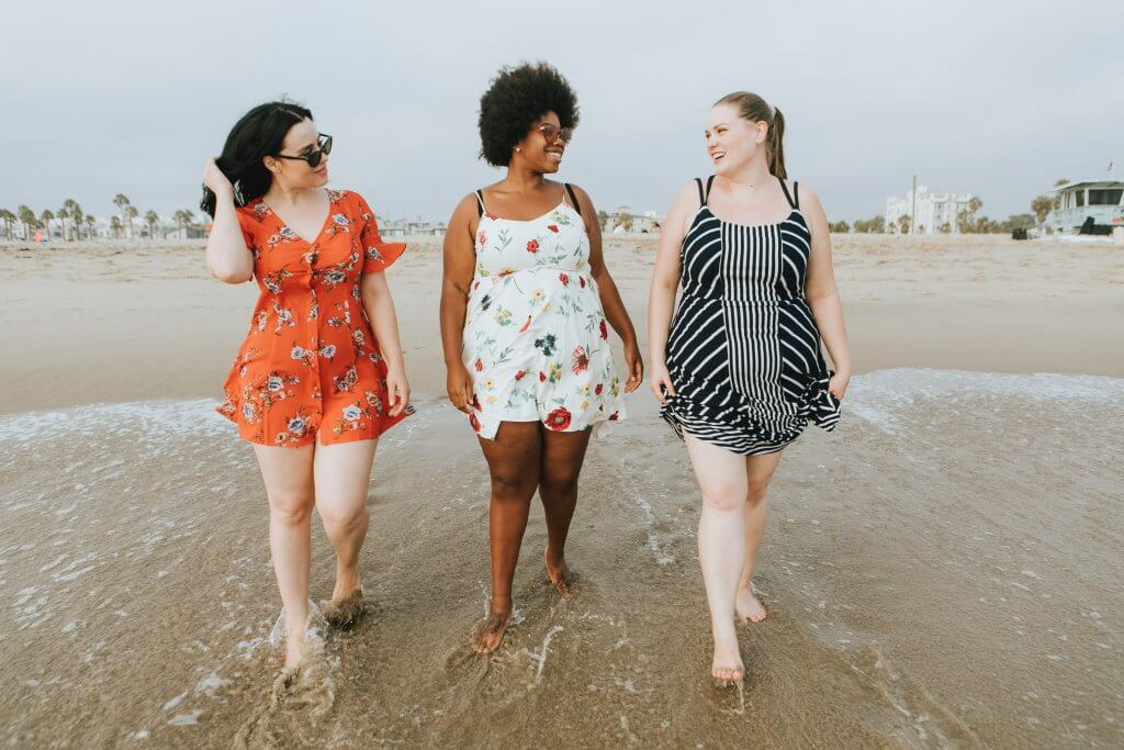 Three women walking along the beach and smiling