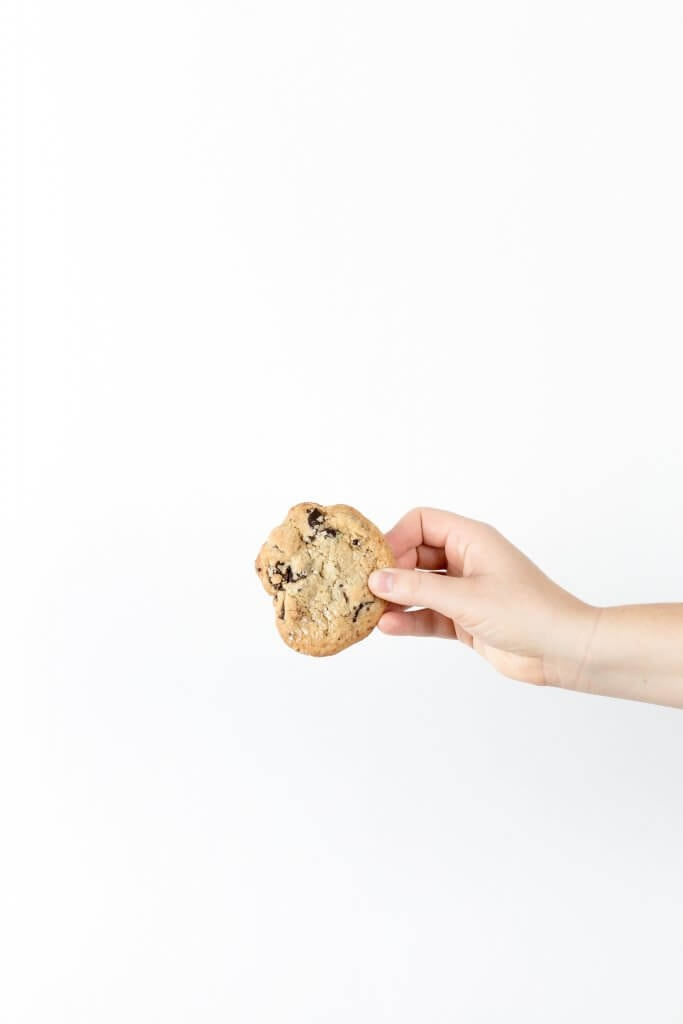 A white background and a person holding one cookie
