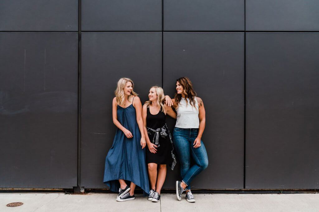 3 women laughing with a black wall behind them