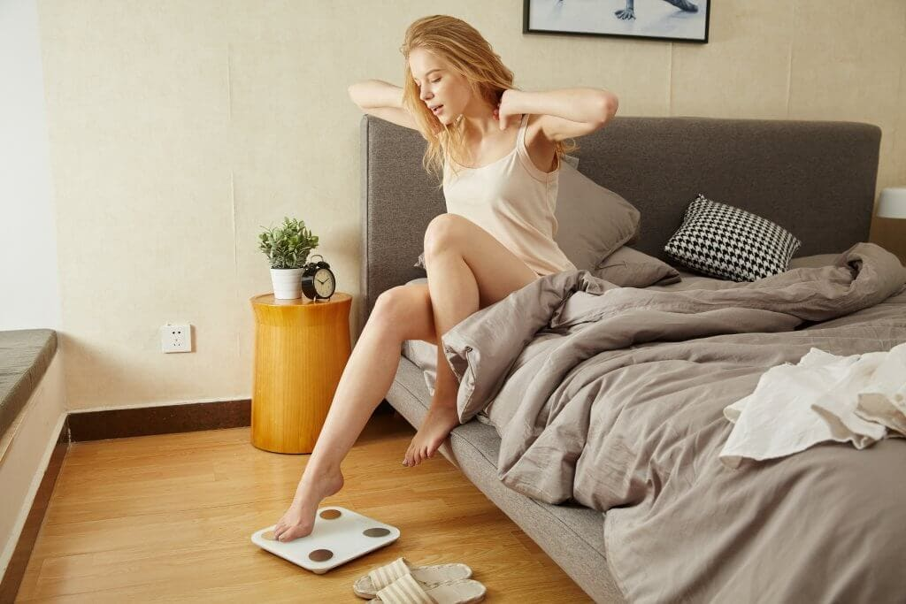 A woman getting out of bed and stepping on the scale
