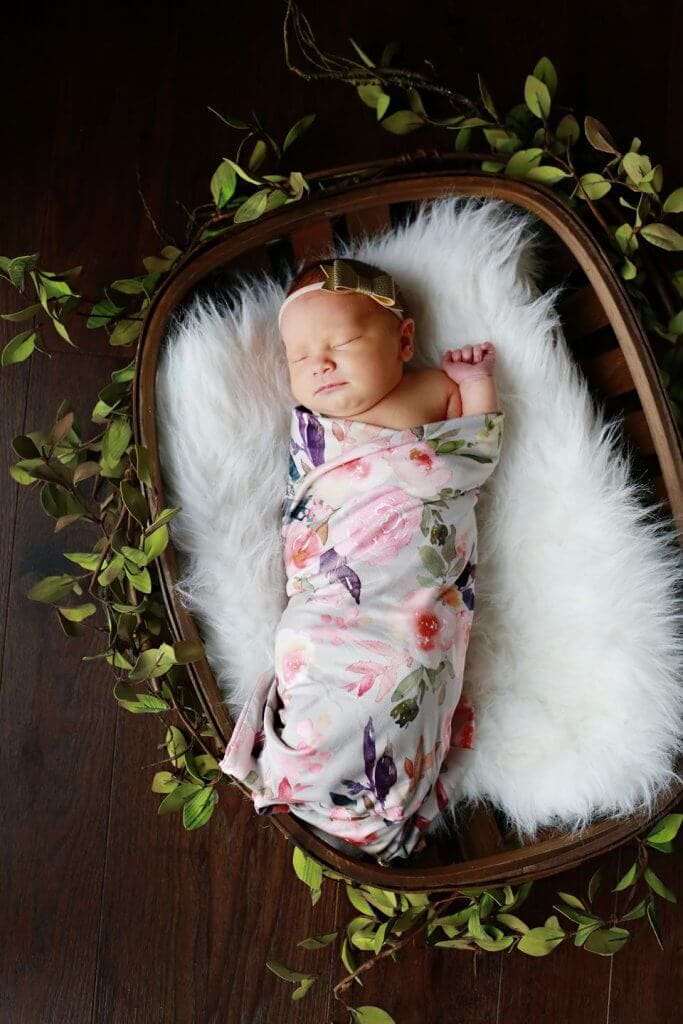 A baby girl in a basket with a white blanket and greenery in a floral swaddle