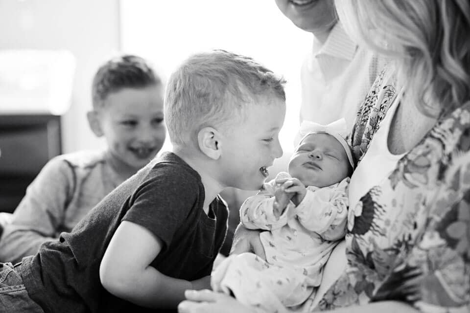 A little boy looking at his baby sister in his mothers arms