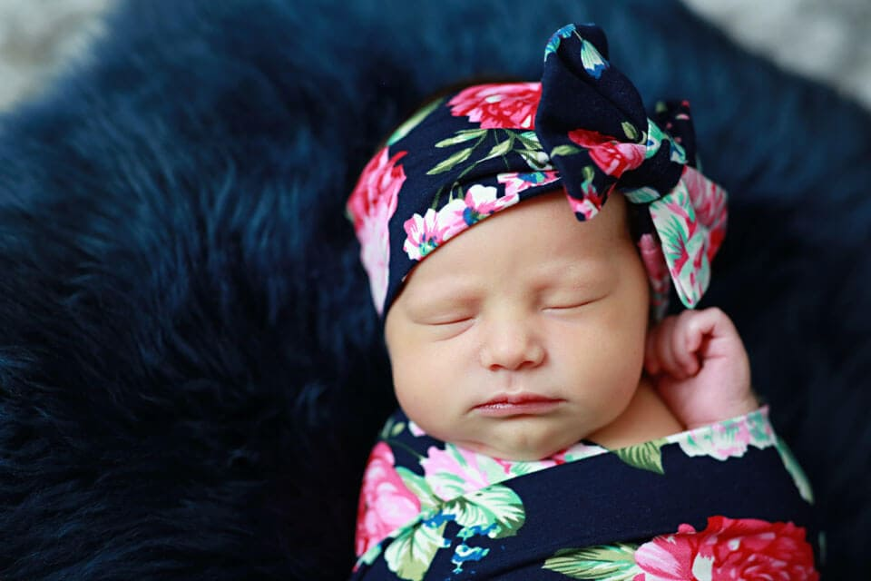 A beautiful little girl with a swaddle and bow