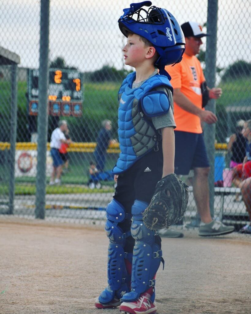 A boy playing catcher in a game of baseball.