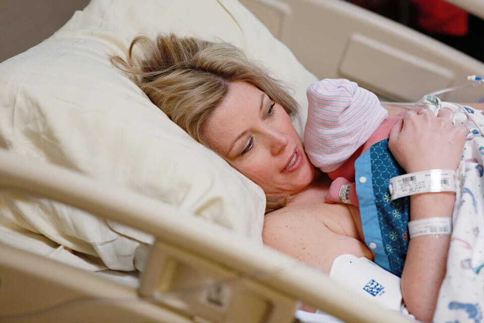 A woman holding her newborn baby in a hospital bed