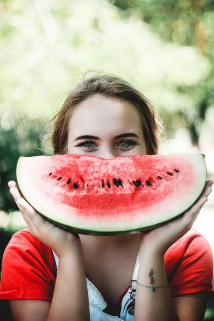 A woman with a watermelon in front of her face