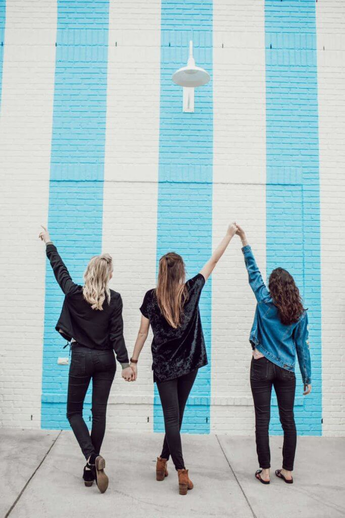 3 girls with their back turned to the camera with a blue stripe wall